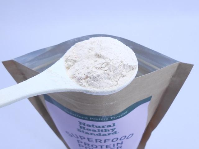 ナチュラルヘルシースタンダードスーパーフードプロテインの粉末をスプーンですくう
